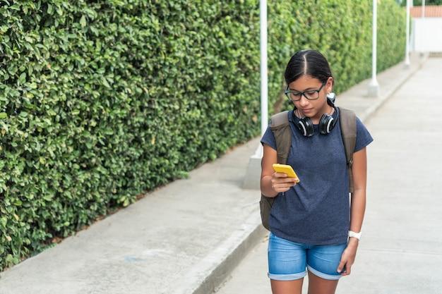공원에서 스마트폰을 확인하는 무선 헤드셋을 가진 10대.