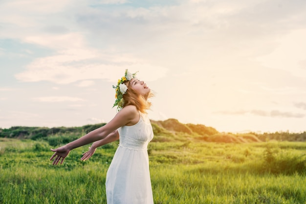 Teenager with wreath enjoying in the meadow