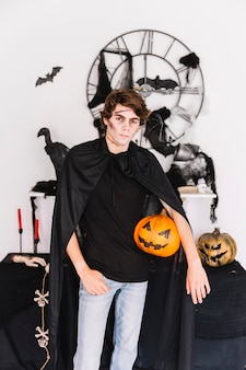 Teenager with zombie grim standing with pumpkin