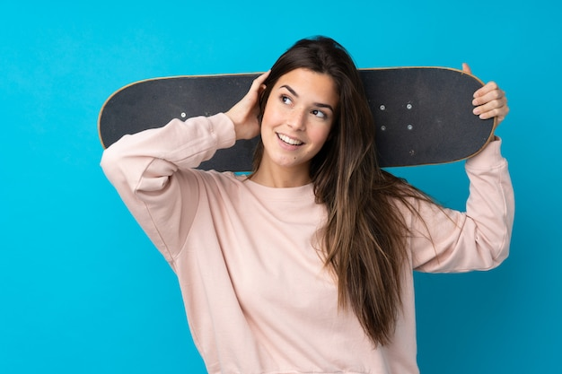 Teenager woman over isolated blue wall with a skate and looking up