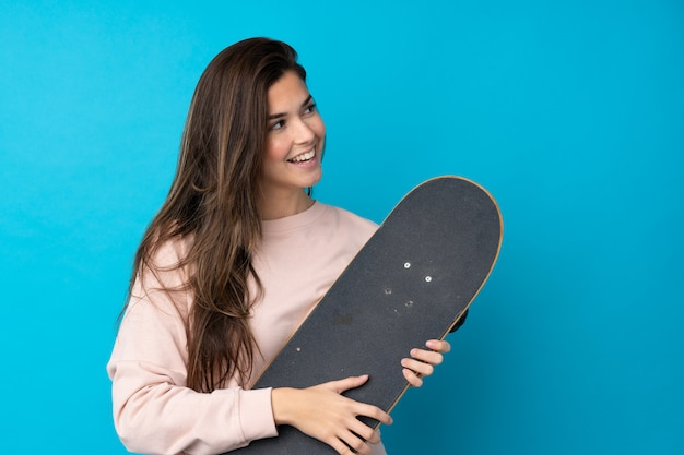 Teenager woman over isolated blue wall with a skate with happy expression