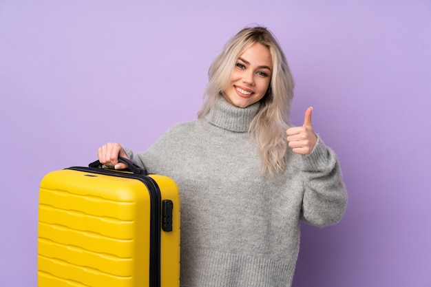 Teenager woman over isolated purple wall in vacation with travel suitcase and with thumb up