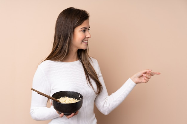 Teenager woman over isolated wall pointing to the side to present a product while holding a bowl of noodles with chopsticks