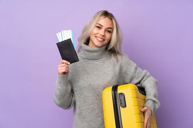 スーツケースとパスポートの休暇で孤立した紫色の壁を越えて10代の女性