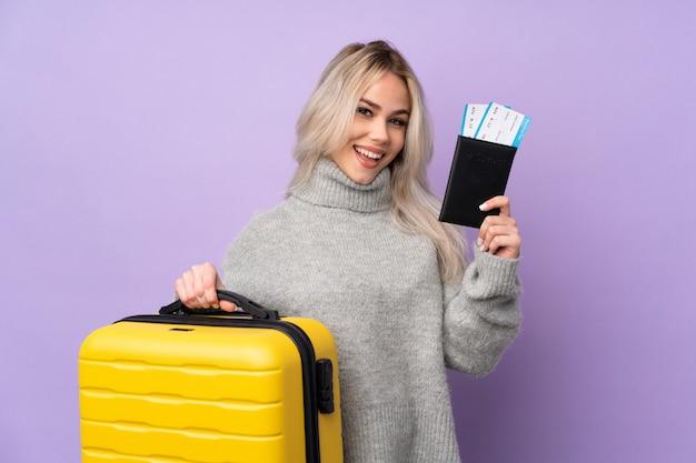가방과 여권 휴가에 고립 된 보라색 벽 위에 십 대 여자