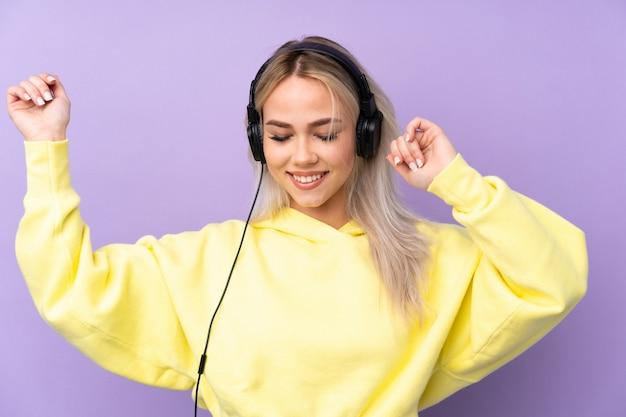 Женщина подростка над изолированной музыкой и танцами фиолетовой стены слушая