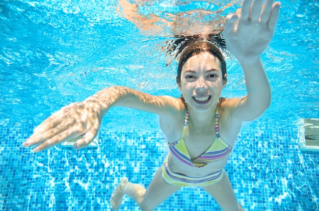 Teenager woman swims underwater in swimming pool, happy active teenager girl dives and has fun under water, kid fitness and sport on family vacation on resort