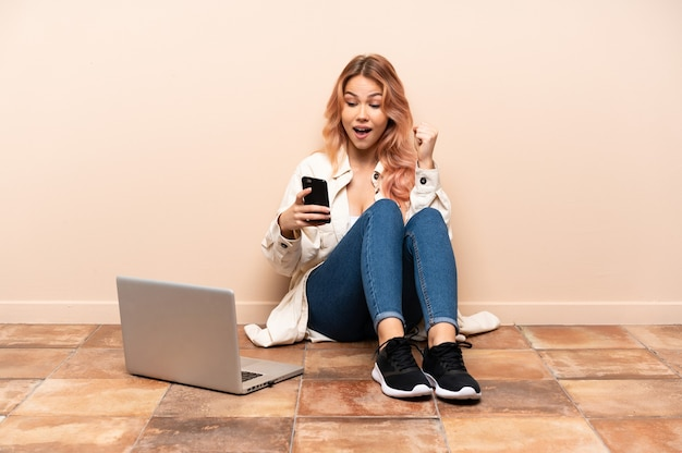 Teenager woman with a laptop sitting on the floor at indoors with phone in victory position