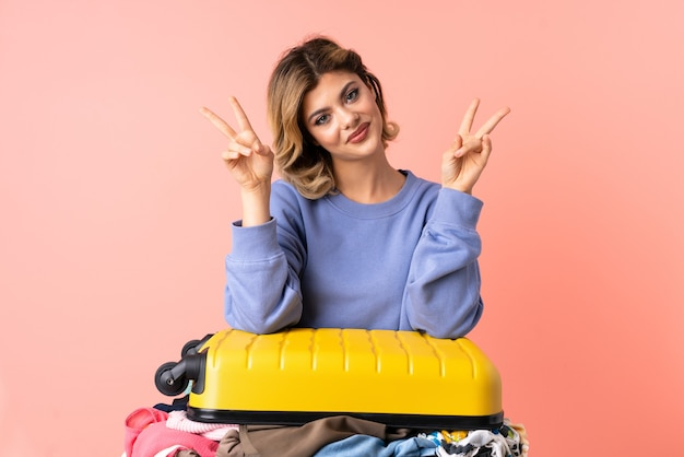 Teenager woman with salad isolated on pink showing victory sign with both hands