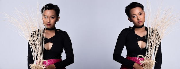 ショートモデルとしてのティーンエイジャーの若いアジア人女性は黒いシャツを着て、ネオンピンクのショートスカートは鼻ピアス、スタジオ照明灰色の背景を分離、コラージュグループパックの肖像画と乾燥した枝の木を開催しました