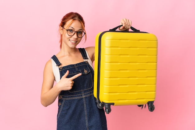 Молодая женщина-подросток изолирована на розовом фоне в отпуске с чемоданом путешествия