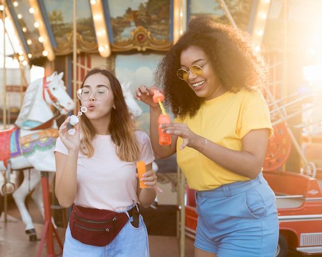 Подростки пускают мыльные пузыри в парке развлечений