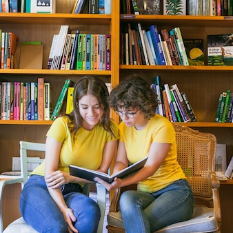 Teenagers on chairs reading book together