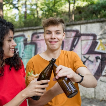 Teenagers cheering with bottles and eating burger outdoors