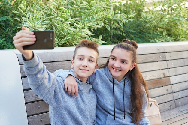 십대 어린이 소년과 소녀는 휴대 전화에서 셀카를 찍습니다. 우정 개념입니다. 가장 친한 친구.