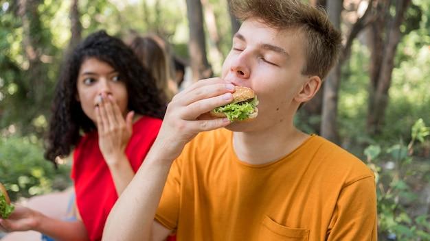 屋外でハンバーガーを楽しんでいるティーンエイジャー 無料写真
