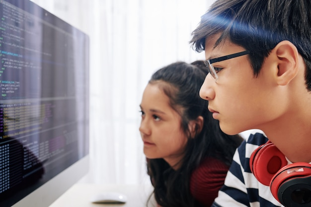 Teenagers examining programming code computer screen