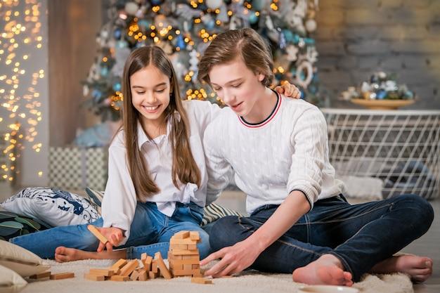 Девочка-подросток и мальчик играют в настольную игру в рождественском интерьере дома