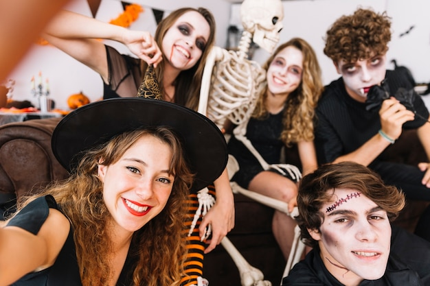 Teenagers in grim and alloween costumes and skeleton doing selfie and smiling