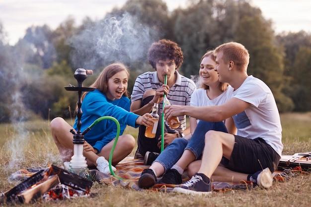 Teenagers have fun. joyful girls and boys spend weekend outdoor on picnic, smoke hookah, clink bottles with energetic drinks