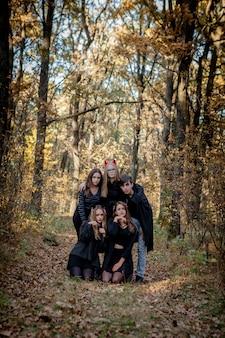 森の中でハロウィーンの衣装を着たティーンエイジャー。