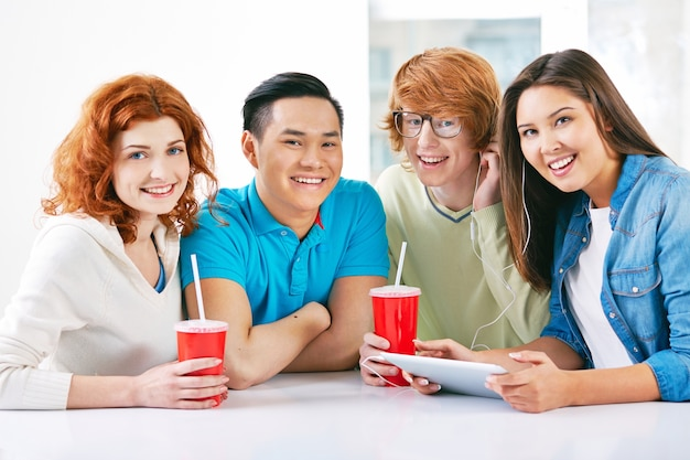 Teenagers laughing with a tablet and some drinks