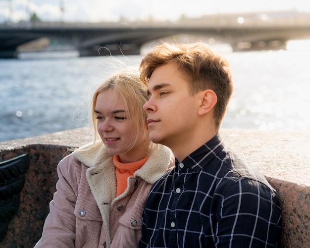 Teenagers in love sit on waterfront in city center, resting in autumn sun. concept first teen love