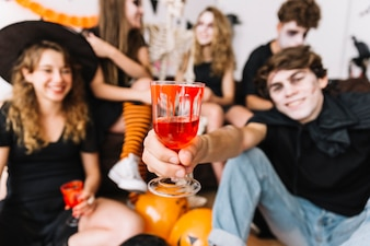Teenagers on Halloween party drinking from glasses with painted blood