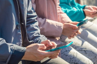 Teenagers play games, write text on phones. Young people are holding smartphones sitting o