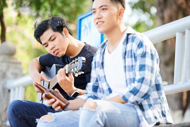 Подростки играют на гитаре на открытом воздухе