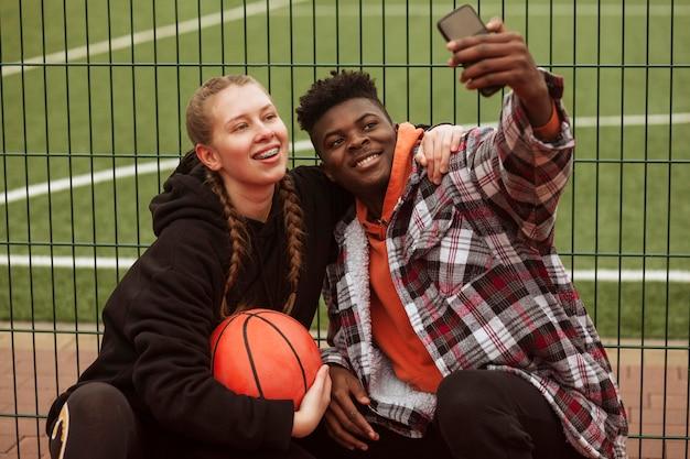 バスケットボールのフィールドでポーズをとるティーンエイジャー