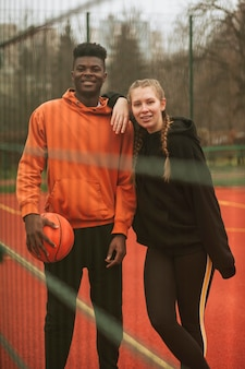 Подростки позируют на баскетбольном поле