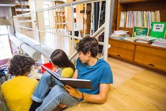 Teenagersreading book near female classmates