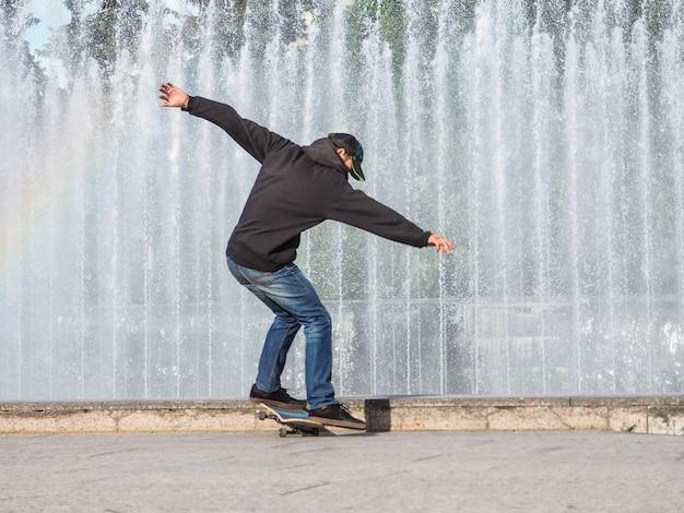 10代の若者はスケートボードに乗ります。スケートボードでのティーンエイジャーのためのエンターテイメント。若者の余暇。アクティブなレクリエーションの概念。