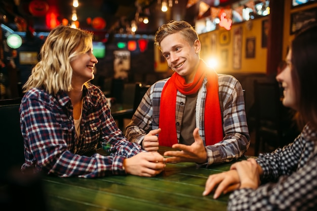 Подростки, сидящие за столом в спорт-баре