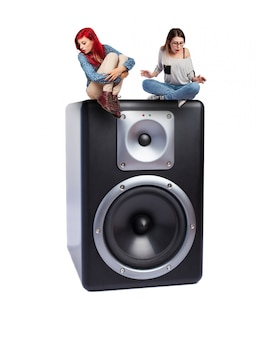 Teenagers sitting on an enormous speaker