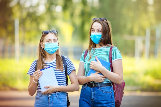Teenagers students girls in medical masks against smog in the city and for protection from coronavirus go on the street in the summer with books to classes. back to school.
