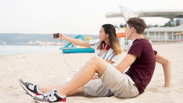 Teenagers taking a selfie together at the beach