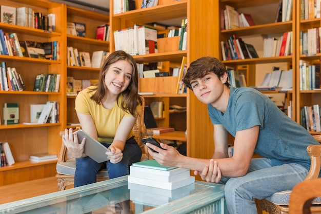 Teenagers with gadgets in library