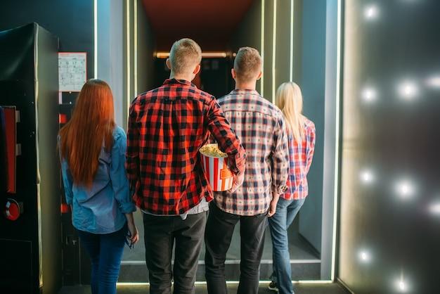 Подростки с попкорном стоят в кинозале перед просмотром, вид сзади. мужская и женская молодежь в кинотеатре
