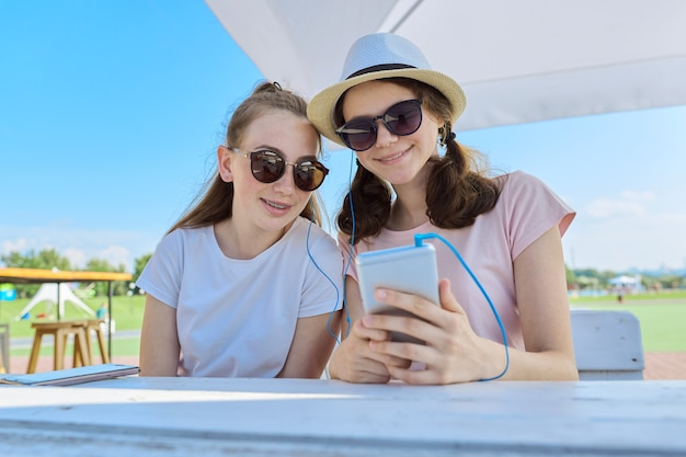 Подростки со смартфонами сидят и разговаривают на открытом воздухе