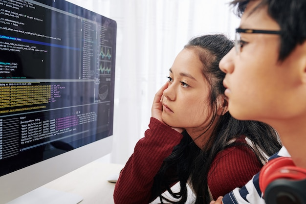 Teenages examining programming code