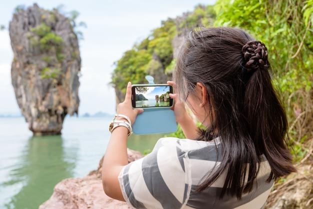 10代の少女観光客が写真のランドマークを撮影し、タプ島またはアオパンガー湾国立公園のジェームズボンド島で携帯電話で美しい景色を眺めることができます。タイの女性旅行自然アジア