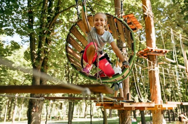 機器を身に付けた10代の若者は、ロープパークや遊び場に登ります。吊橋に登る子供たち