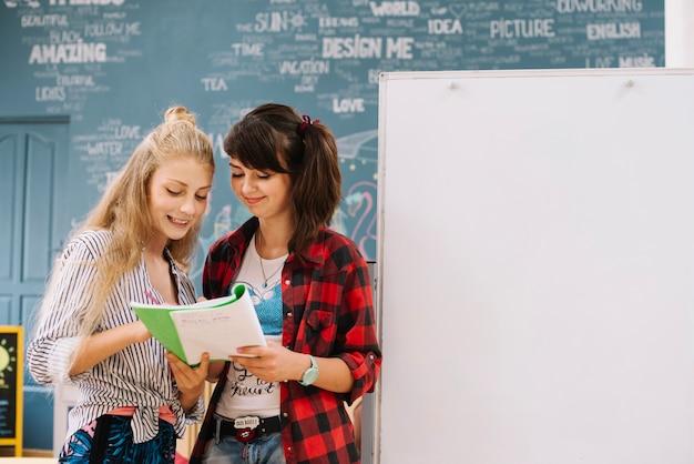 Подростки читают книгу на доске