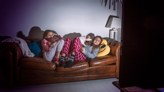 Teens relaxing in living room with tv