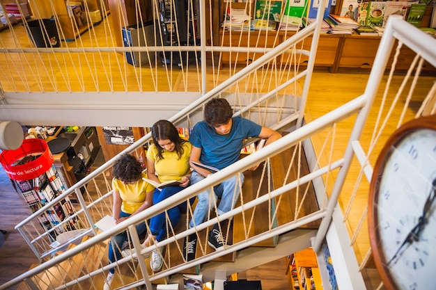 Teens with books relaxing on staircase