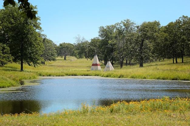 オクラホマ州の湖の背後にあるティーピー