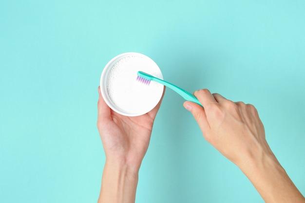Уход за зубами. женские руки, держа зубную щетку и зубной порошок на синем. вид сверху