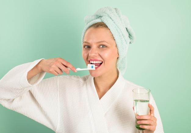 Уход за зубами гигиена стоматологическая гигиена уход за полостью рта чистка зубов женщина чистит зубы в ванной утром